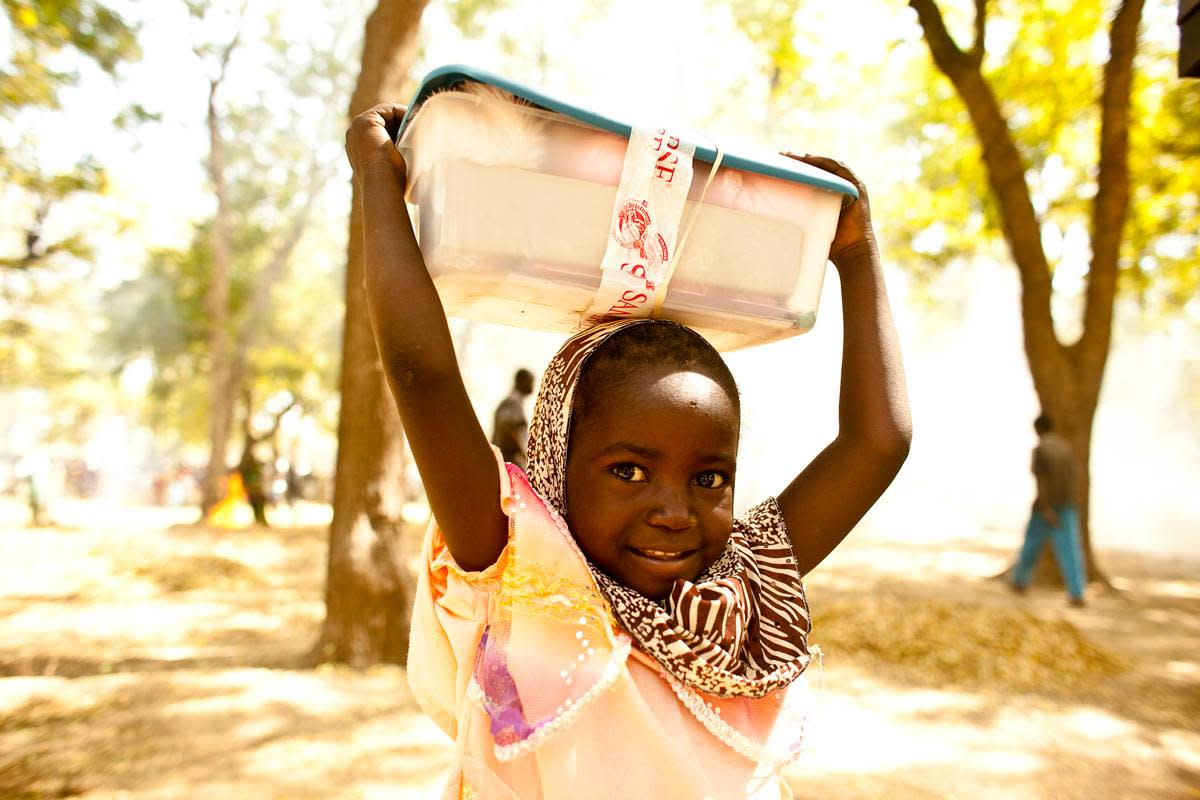 A girl carrying her OCC shoebox on her head in Cameroon.