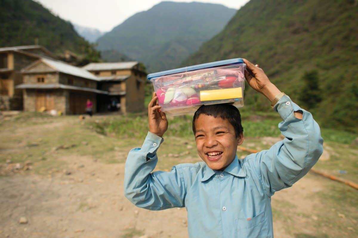 A boy holding his shoebox.