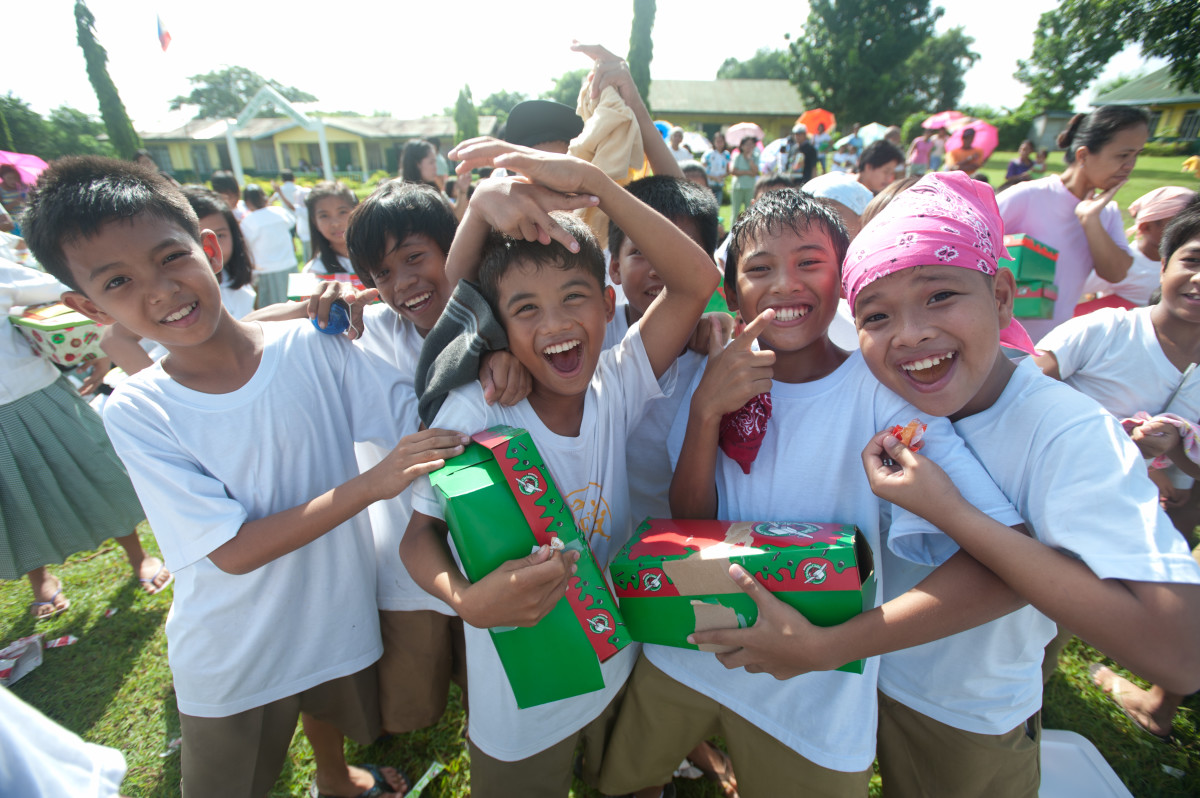 Older boys celebrating their shoeboxes at an OCC distribution event.