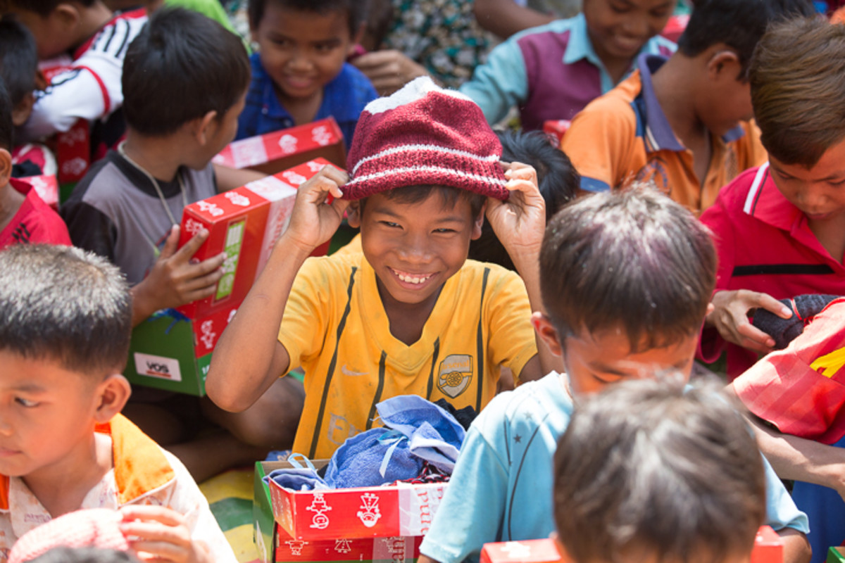 A boy tries on his new beanie at an OCC distribution event in Asia.
