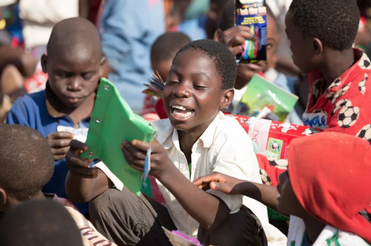 A boy in Malawi holds the pencil case that was packed in his shoebox.