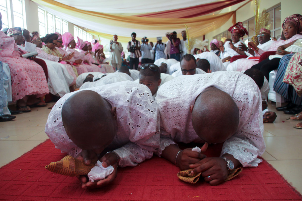 The groom and friends prostrating in front of the parents and elders of the bride.