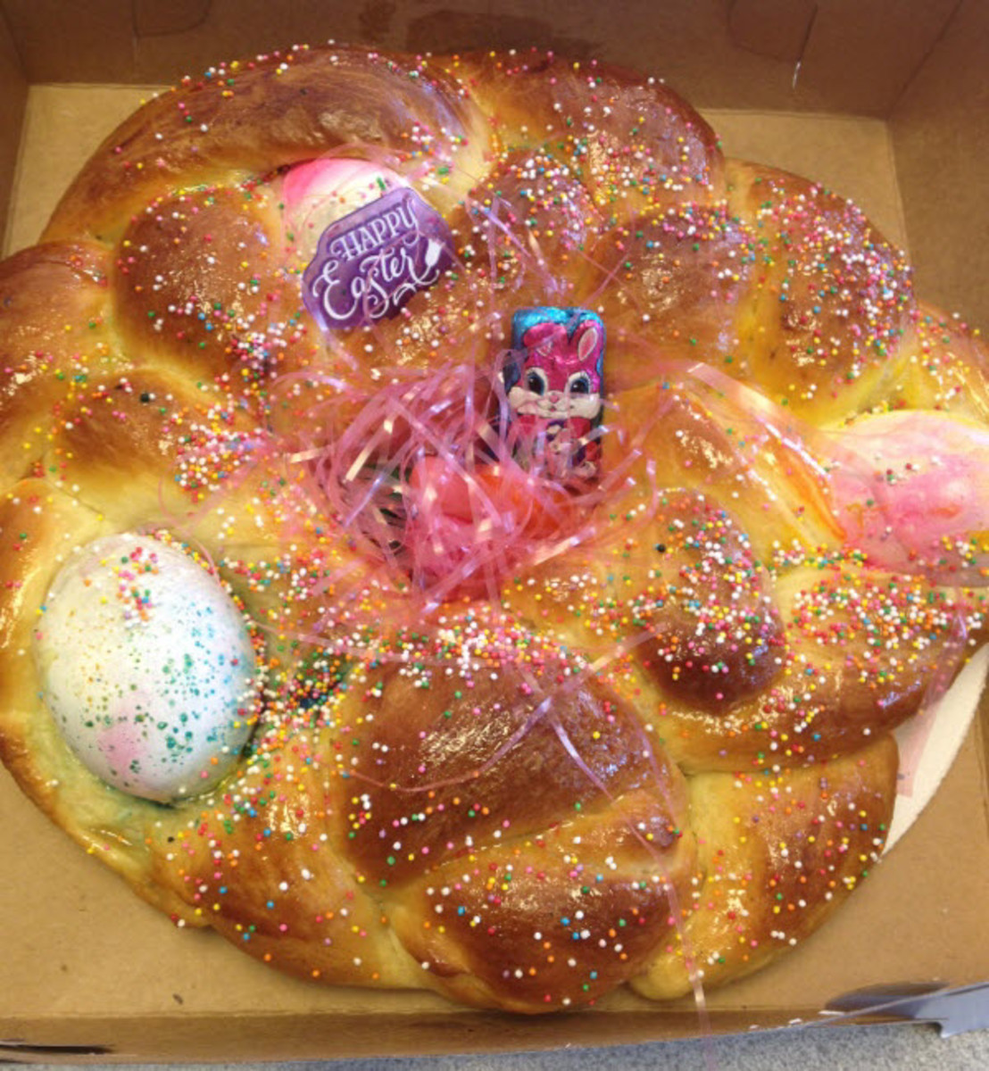 A loaf of Easter bread topped with Easter trinkets.
