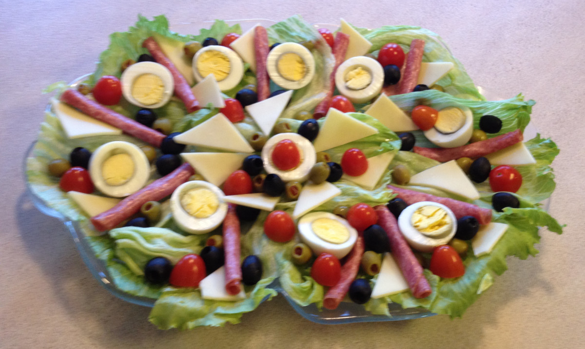 A traditional antipasto platter that includes eggs, salami, cheese, tomatoes, olives, and lettuce.