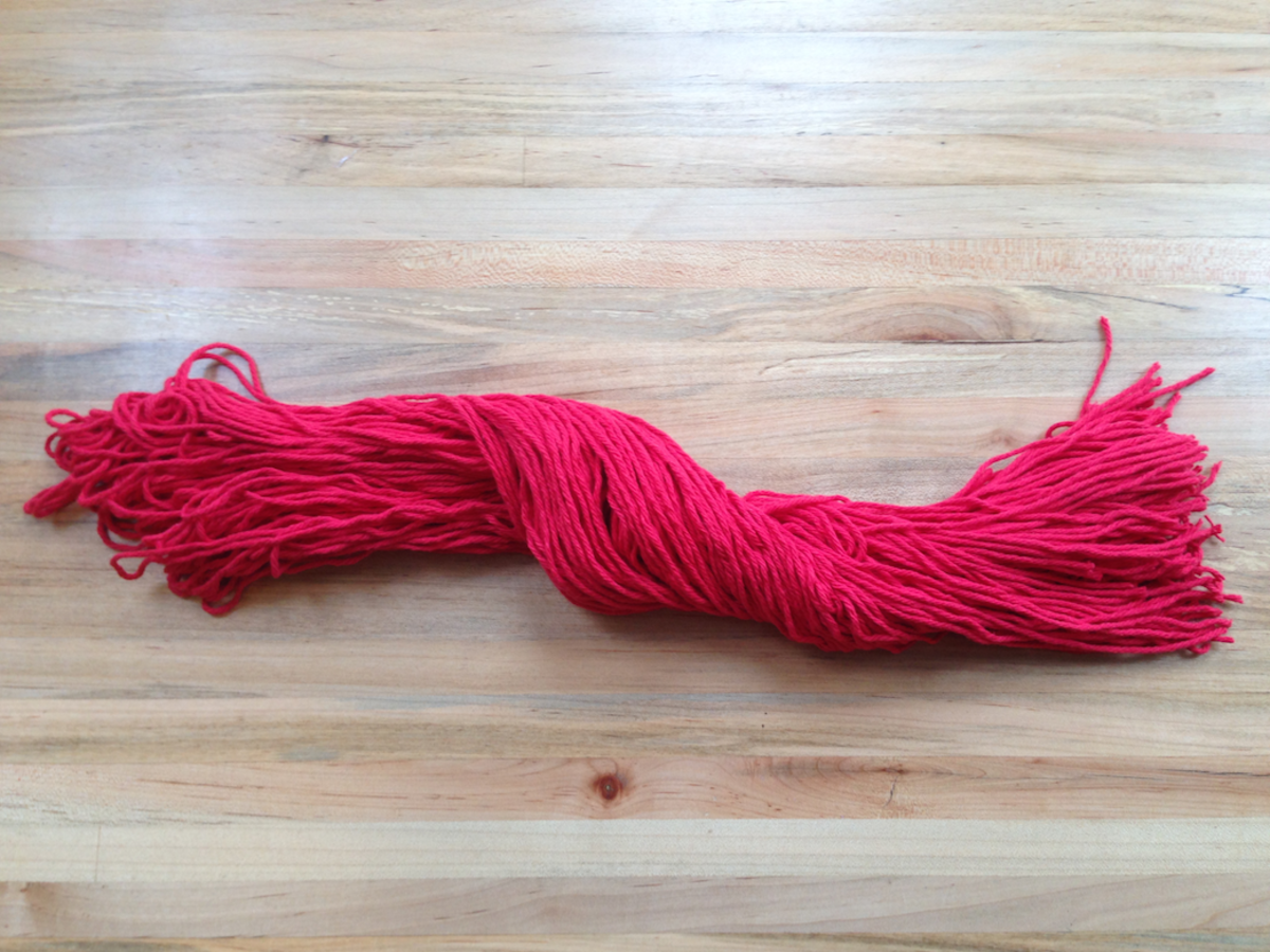 Cut the red yarn into equal lengths in order to make the hair.