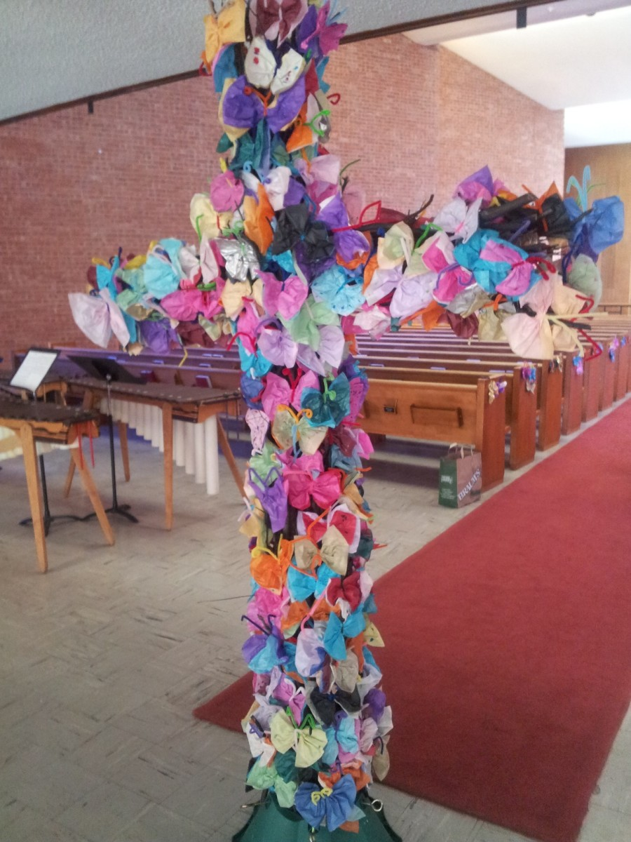 The cross decorated for Easter using tissue-paper butterflies.