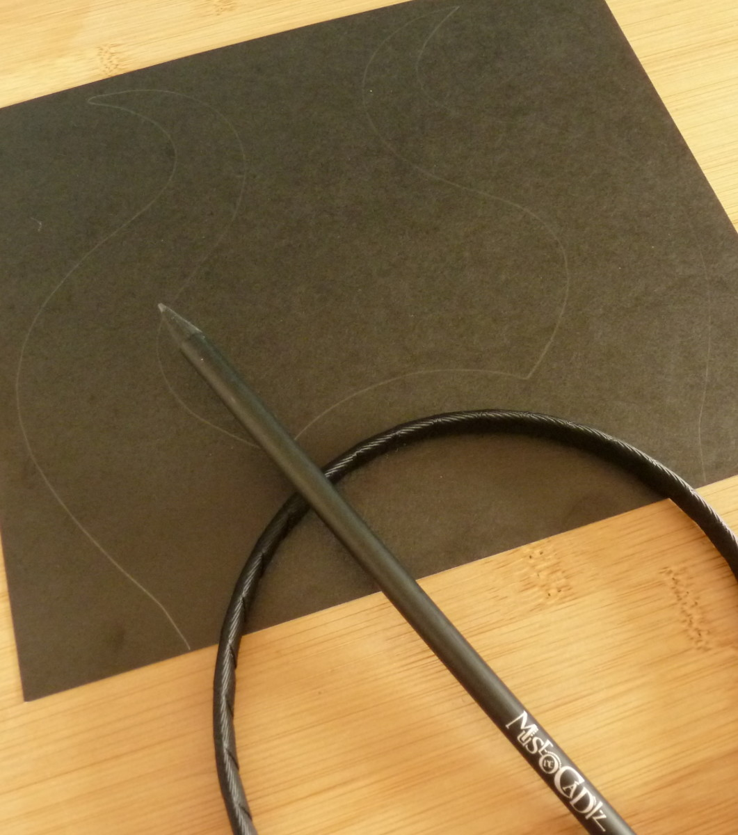 Tracing around the template design onto black card with a pencil