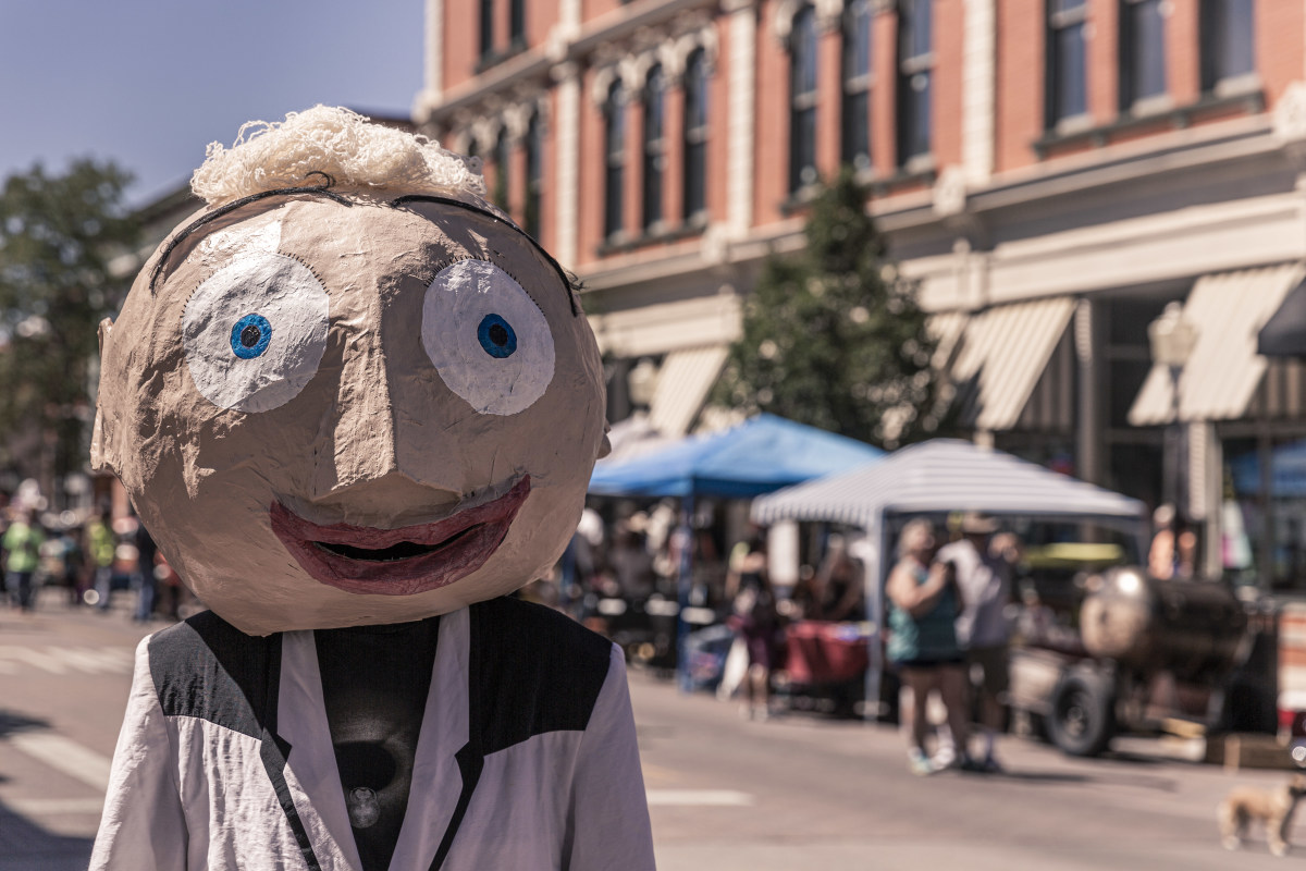 A young man wearing an  over-sized paper mache head  as a mask to complement a wrinkled lightweight jacket and tee shirt.