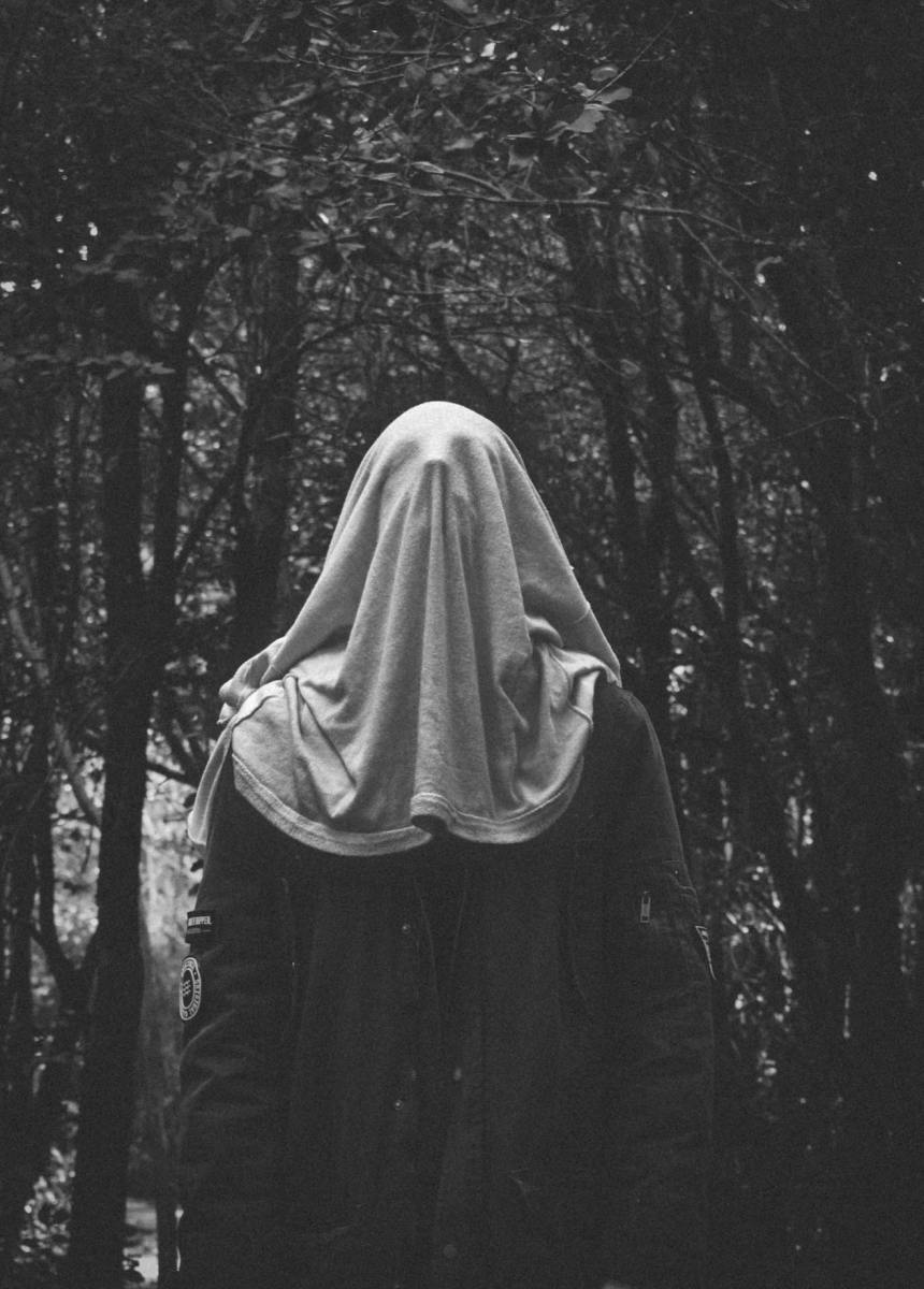 A man wearing a simple white cloth over his head presents a ghostly figure.