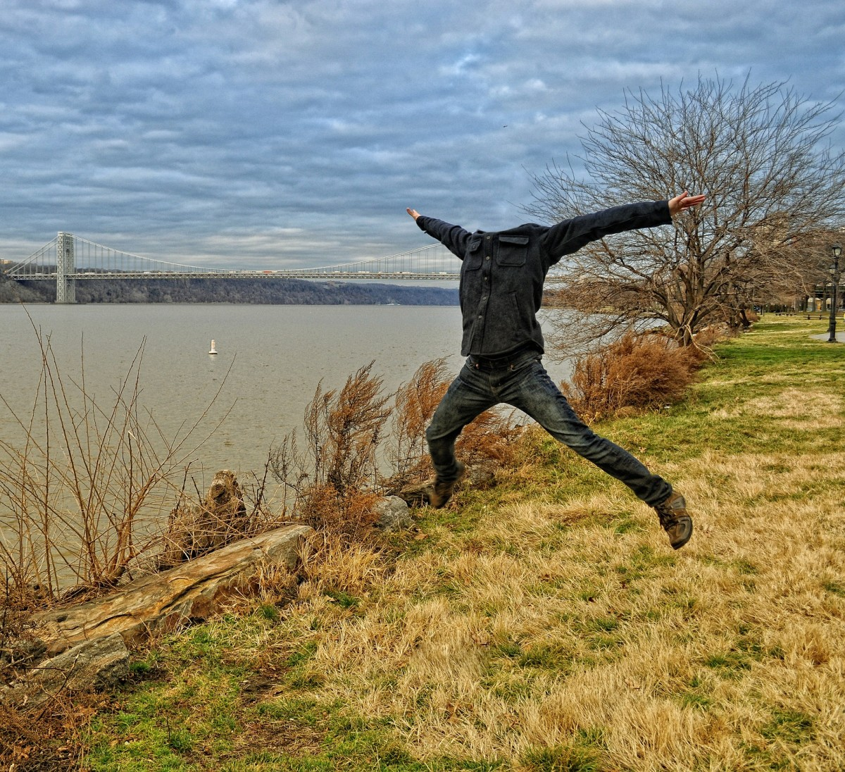 A headless man dressed in everyday clothing jumps about in an open field.