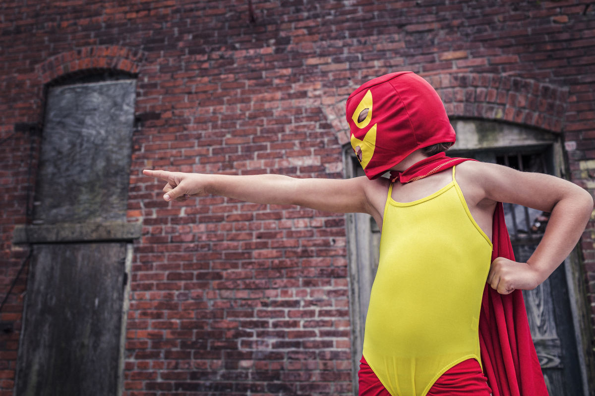 A young man wearing a red hood with a stitched mask, a red cape, red leggings, and a yellow body leotard representing his favorite super hero.