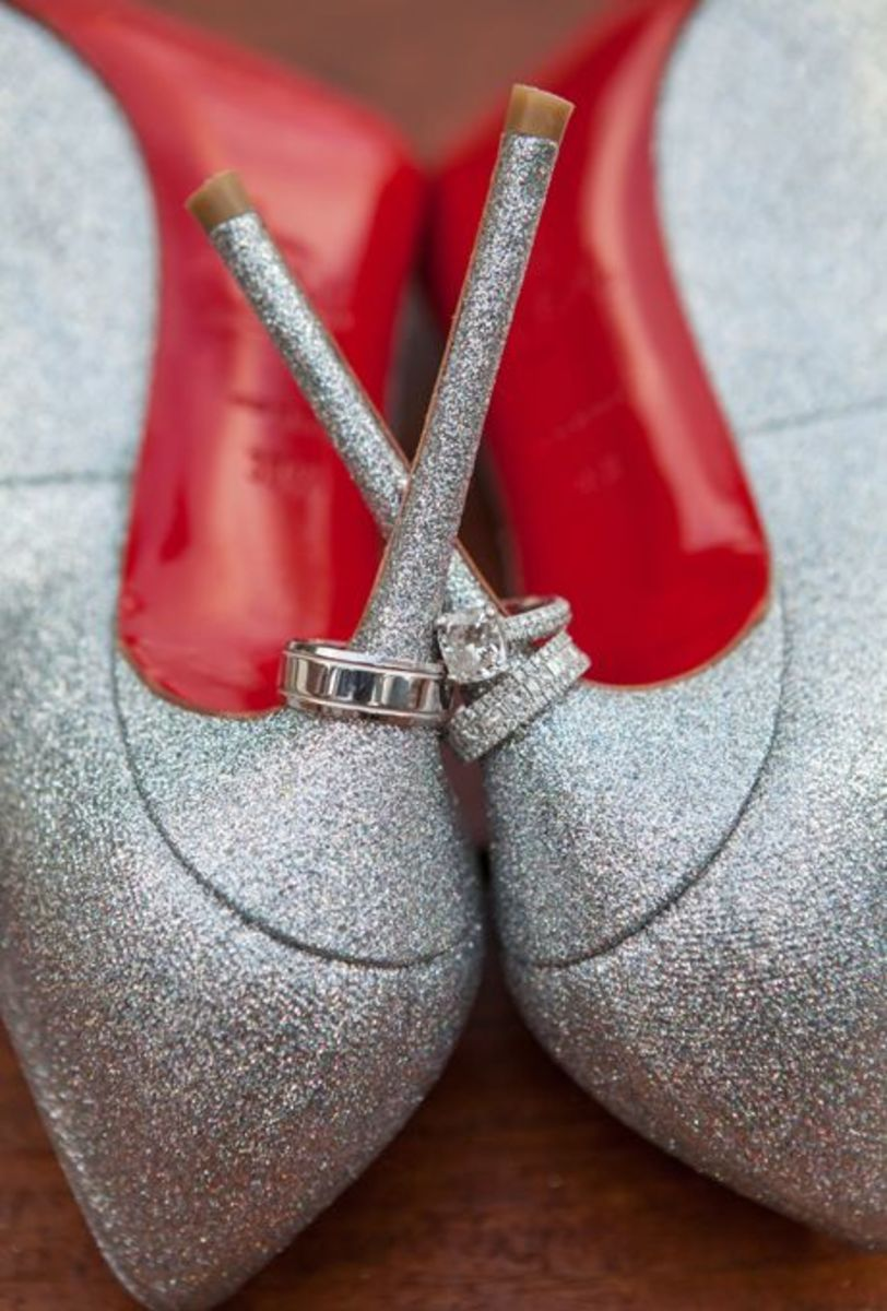Gorgeous wedding rings on silver high heel shoes with red lining