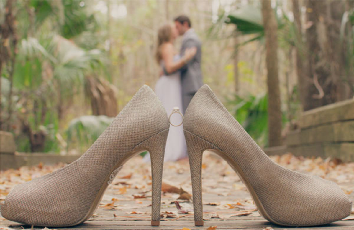 A couple kissing with wedding ring held between two high heeled shoes