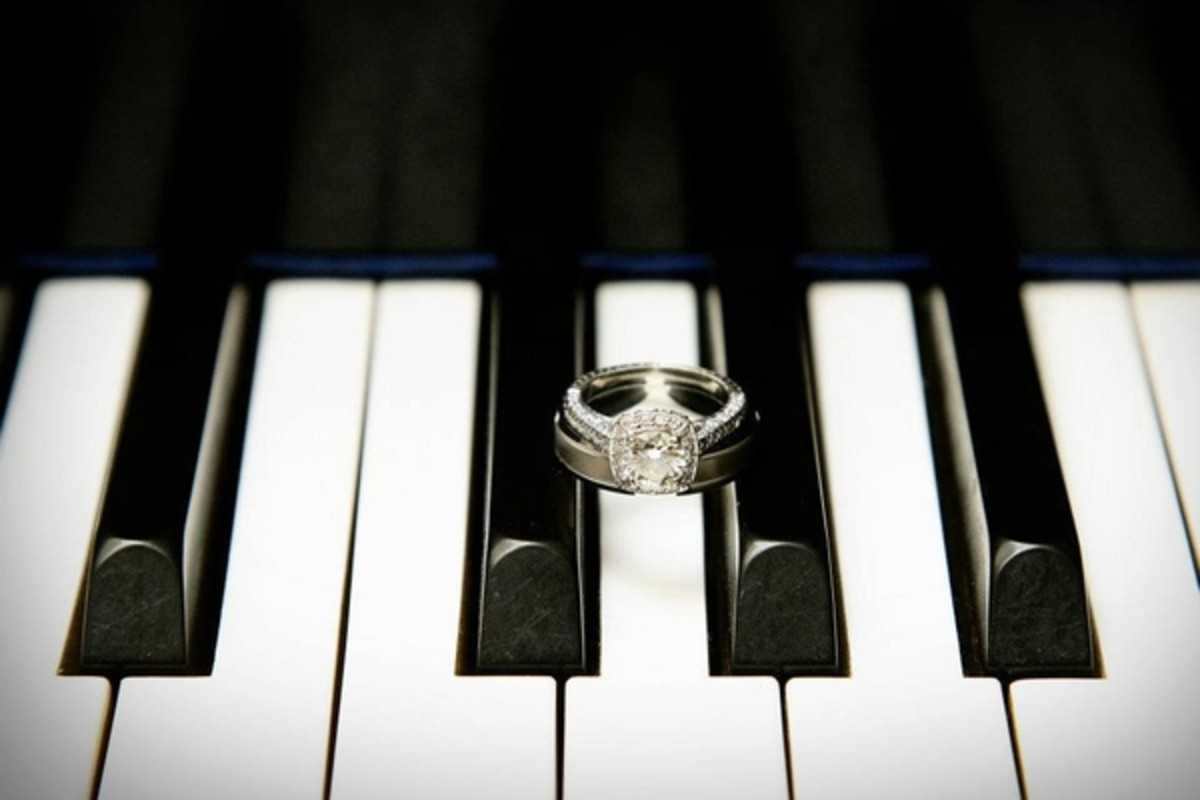 Black and white photograph of her wedding ring between piano keys