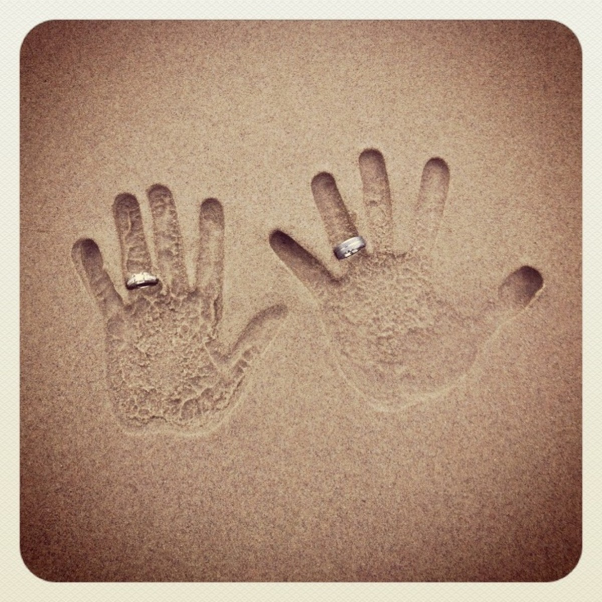 His and her handprints with rings on sand