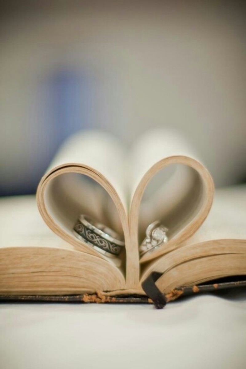 His and her wedding rings with a book