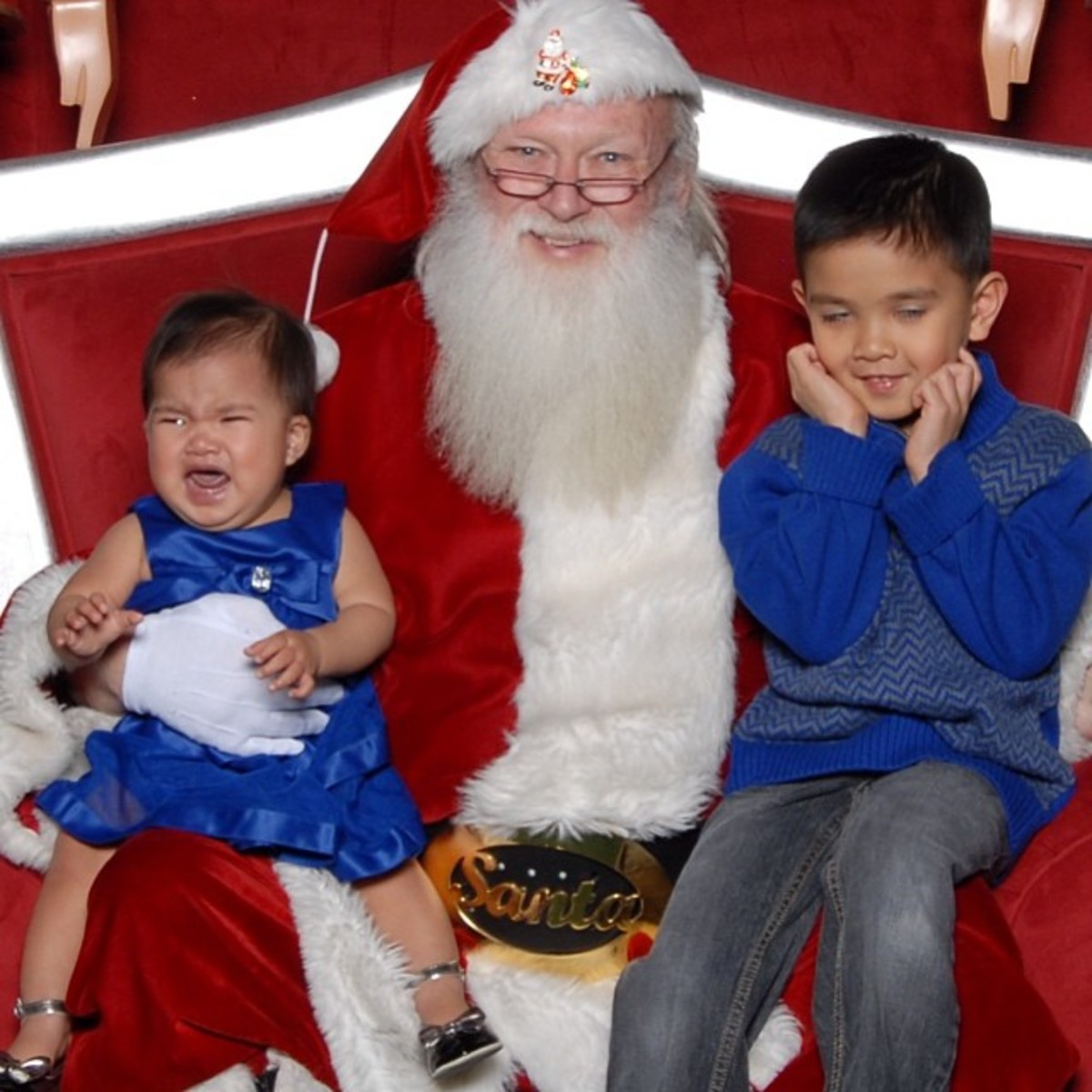 The older brother's expression is priceless, and Santa is taking pride in the terror he is inflicting.  Does Santa have a dark soul?