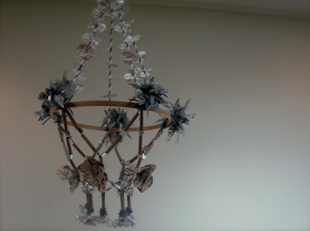 The surprisingly elegant chandelier my daughter and I made of tin foil, newspapers, paper straws, mirrors, yarn, tissue paper, twine, and part of an embroidery hoop.