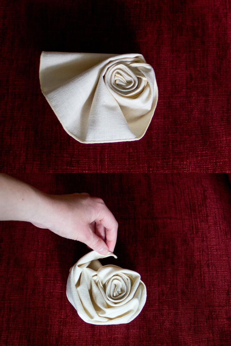 The final steps of folding a cloth napkin into a rose.