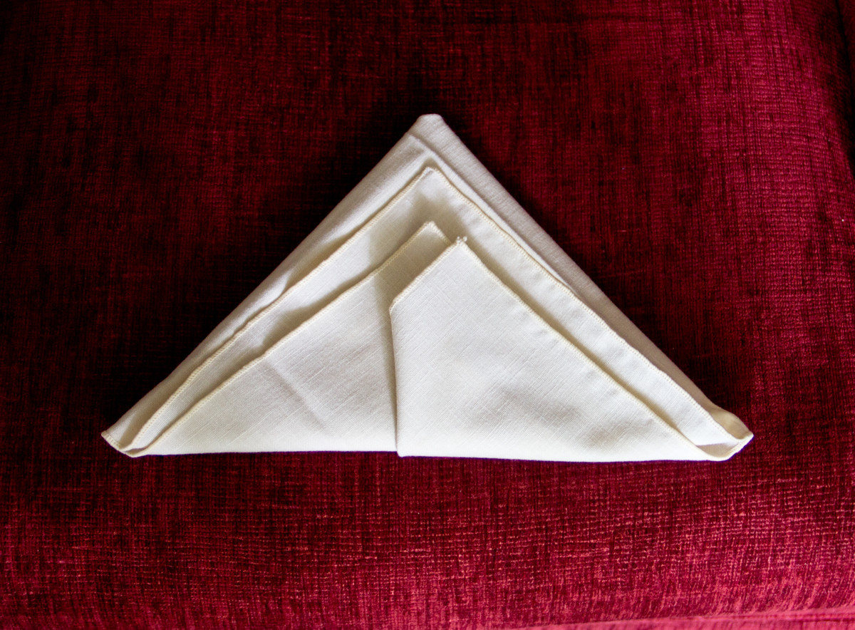 The almost final step of the classic napkin fold.