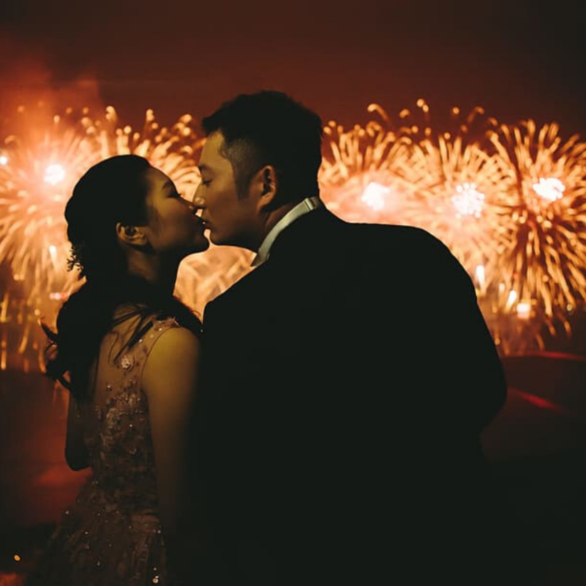 Midnight fireworks and kisses are both popular New Year's traditions.