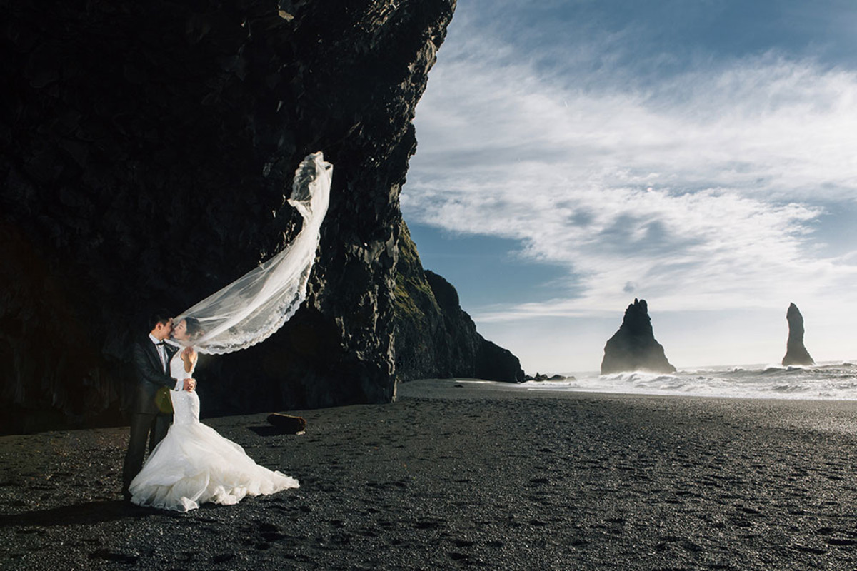 black sand beach in Iceland gives a romantic aura to this wedding photo...