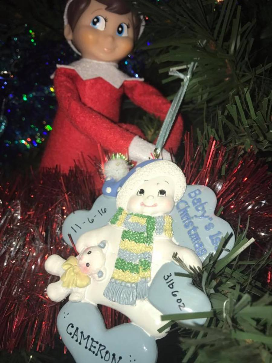 Elf on the Shelf helps hang baby's ornament!