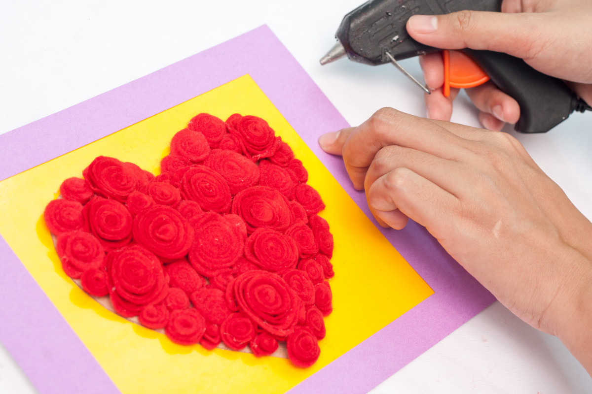 Step 10: Glue your frame in place around the outside of your rose filled heart. Using hot glue, glue the border or frame to the piece of cardboard with the roses on it.