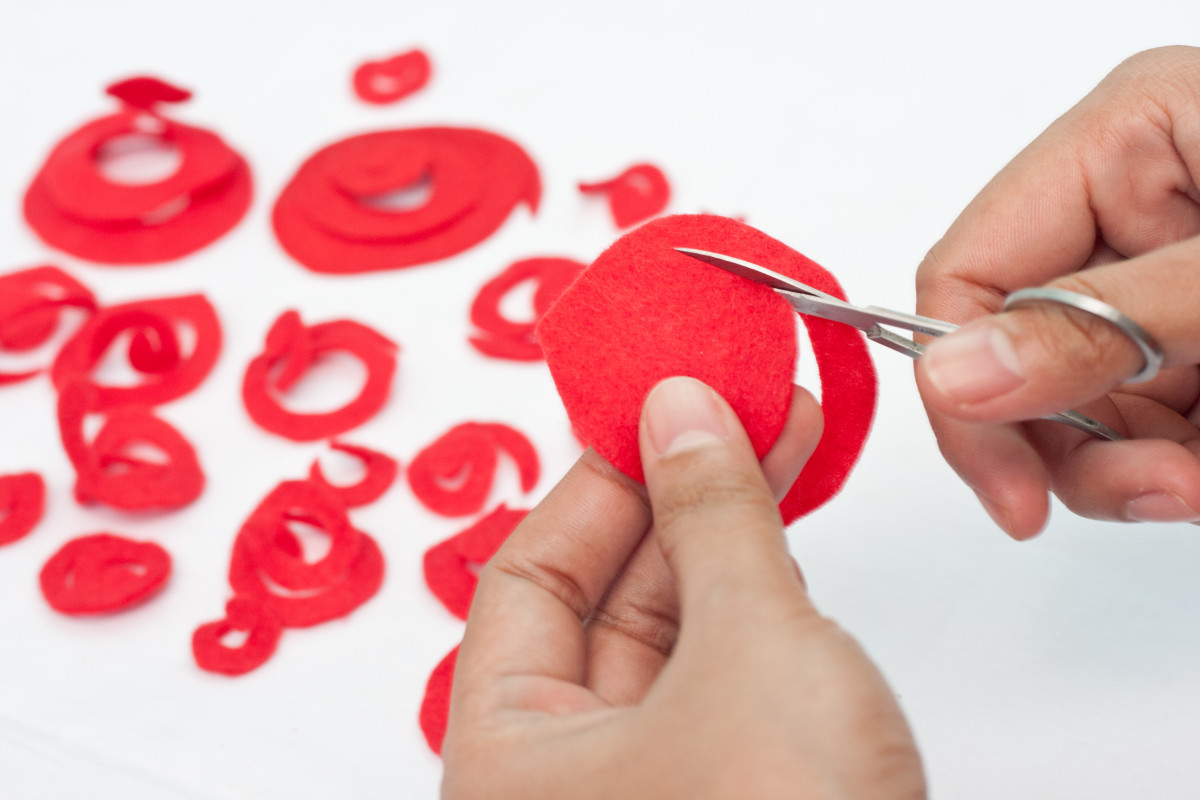 Cut your red circles into strips as shown - start from the outside and work your way in with the small scissors