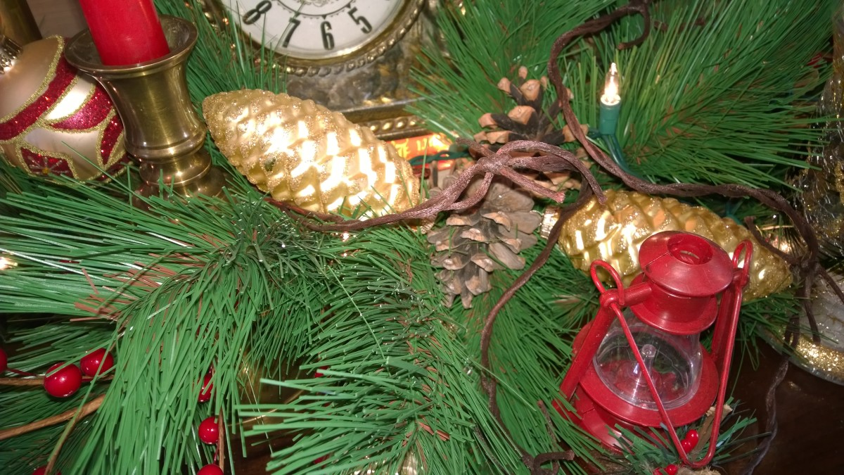 "Evergreen garland with golden pine cones flanked by antique barbed wire that was out behind the barn and tiny lanterns purchased from the local ""dollar store""."