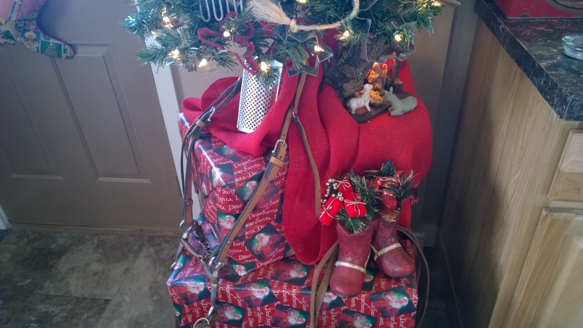 Large empty boxes wrapped with Christmas paper form a stand for a small tree which has been decorated with items like cookie cutters, bits of rope, an antique horse bridal, and a couple of red boot shaped kitchen utensil holders filled with garland.