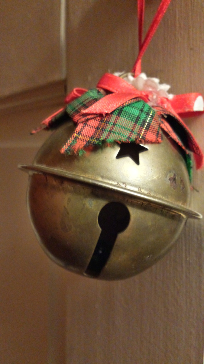 Close up of an oversized jingle bell topped with red and plaid ribbon and white mistletoe flowers.