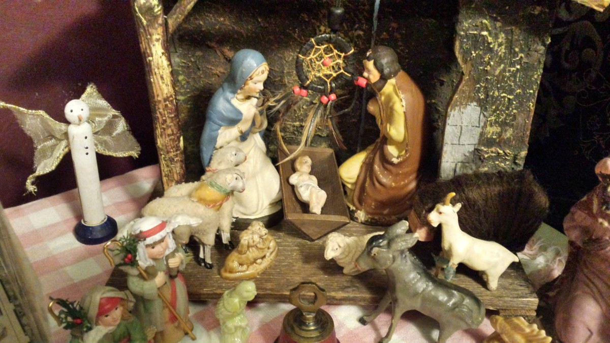 Antique creche featuring Mary, Joseph, and baby Jesus alongside sheep, shepherds, a donkey, and a single wiseman.  A snowman angel sits to one side, there is a dreamcatcher over the baby, and a Christmas bell in front of the scene.