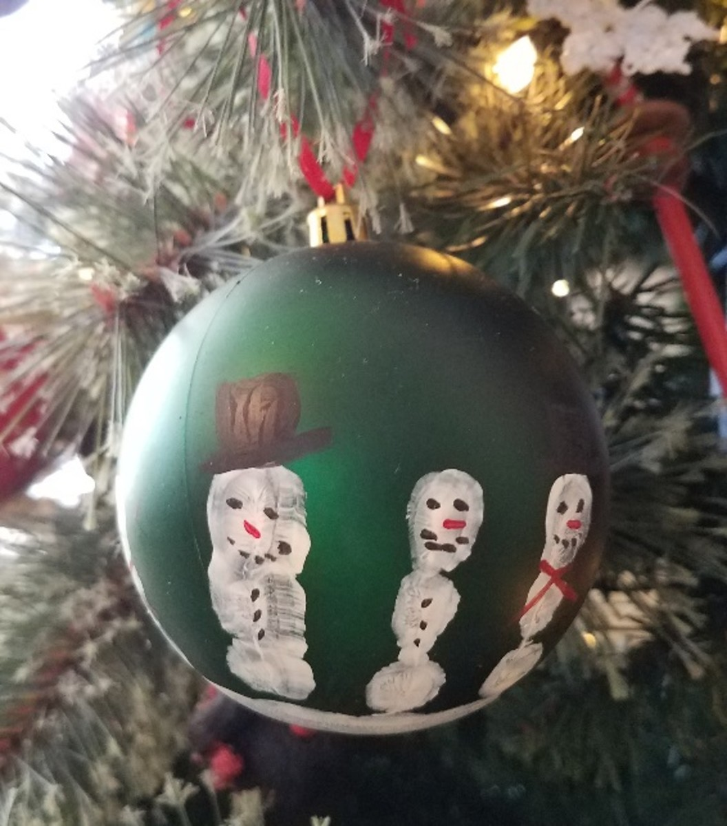 Turn thrifted ornaments into personalized handprint snowmen.