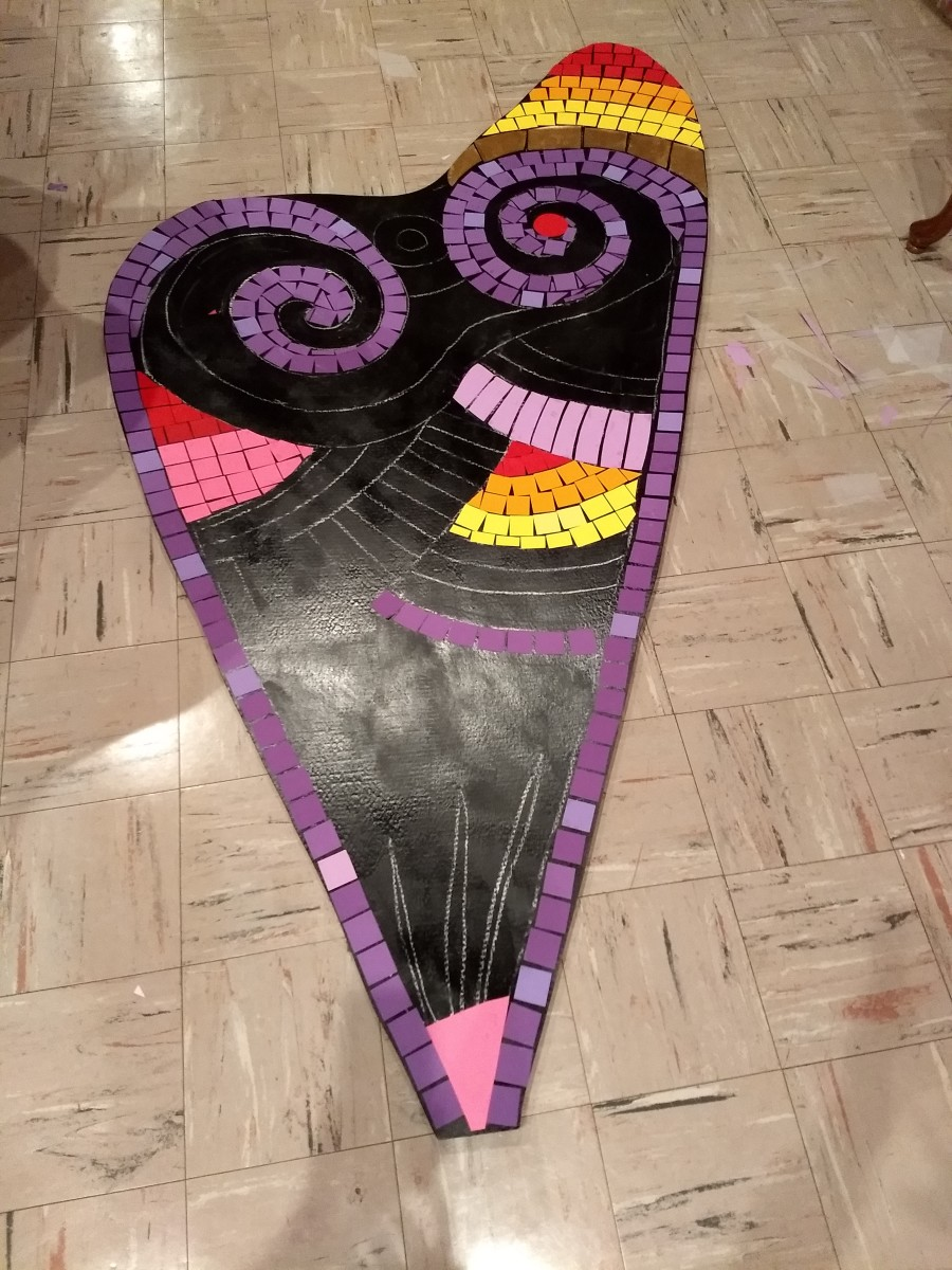 Colored paper being placed onto the cardboard base.