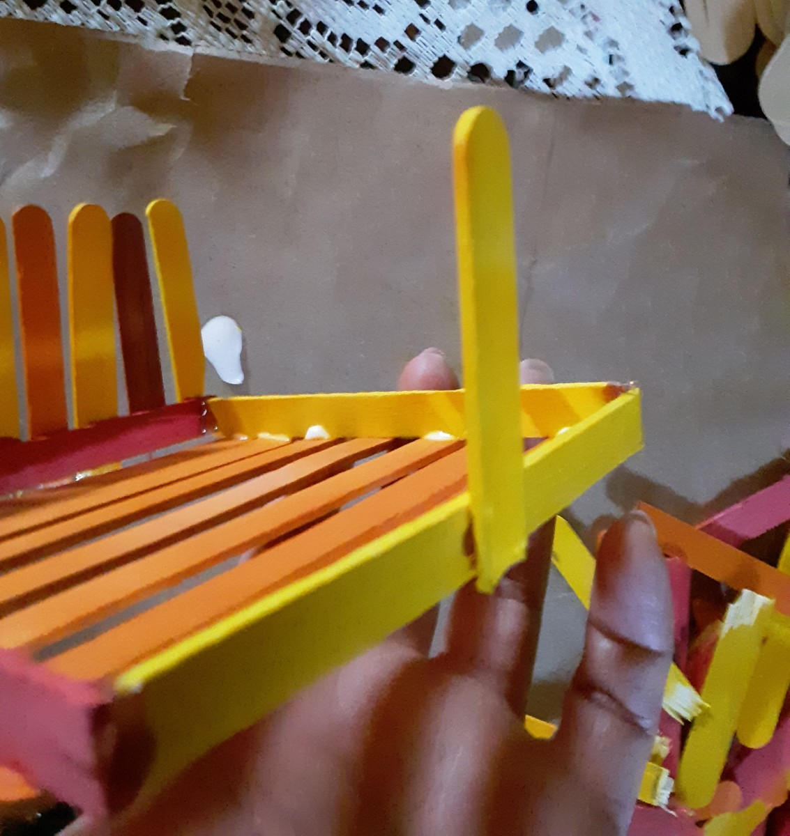 Glue each half of a popsicle stick along the bottom, to create the walls of basket.
