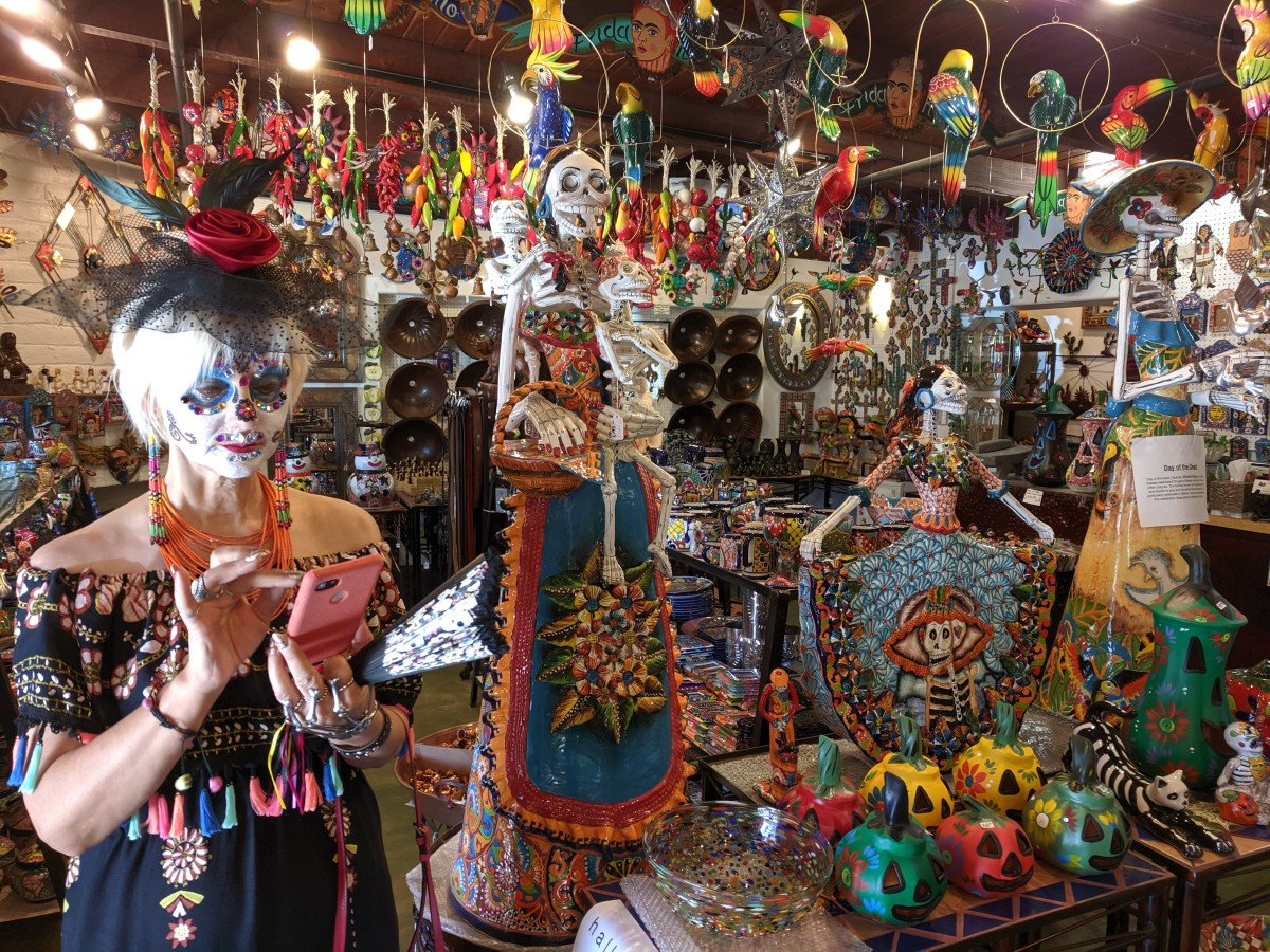 My wife preparing to take a picture of the el Dia de los Muertos merchandise surrounding her