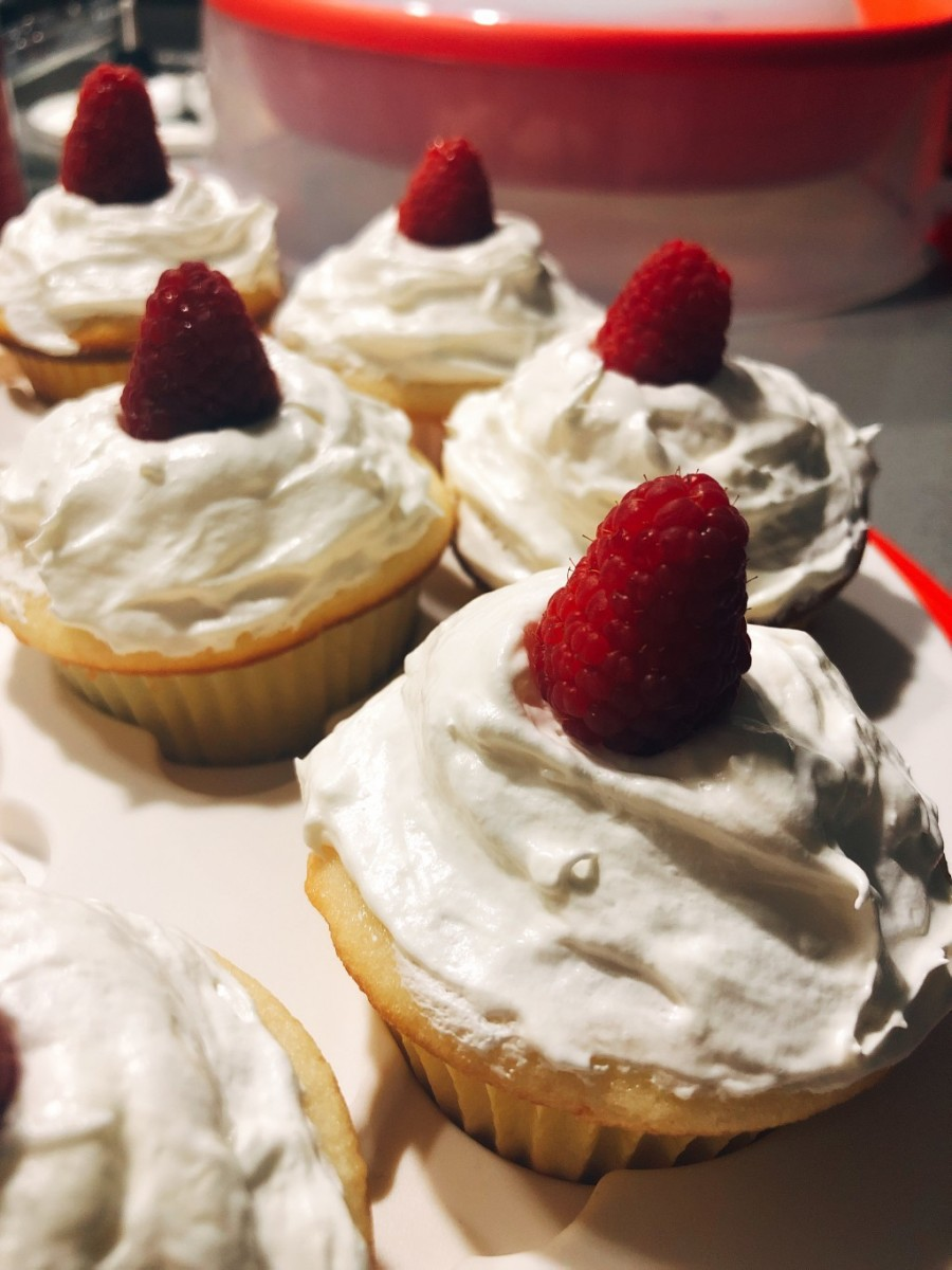 Fluffy and soft vanilla cupcakes with simple vanilla frosting topped with red raspberries
