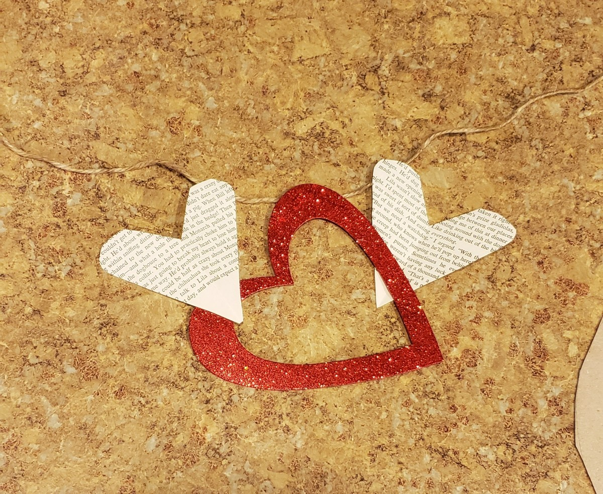 Continue gluing your hearts to your twine, alternating sparkle hearts with book page hearts.