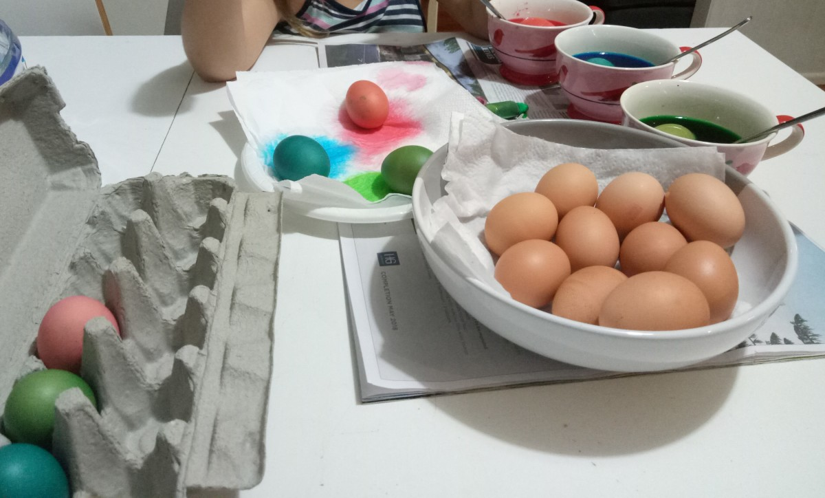 Here, some coloured eggs are drying on a paper towel while some dry eggs have already been placed in the carton.