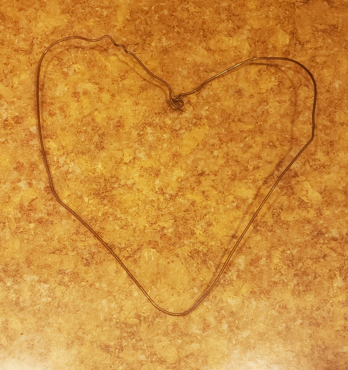 Bend your wire hanger into a heart shape.