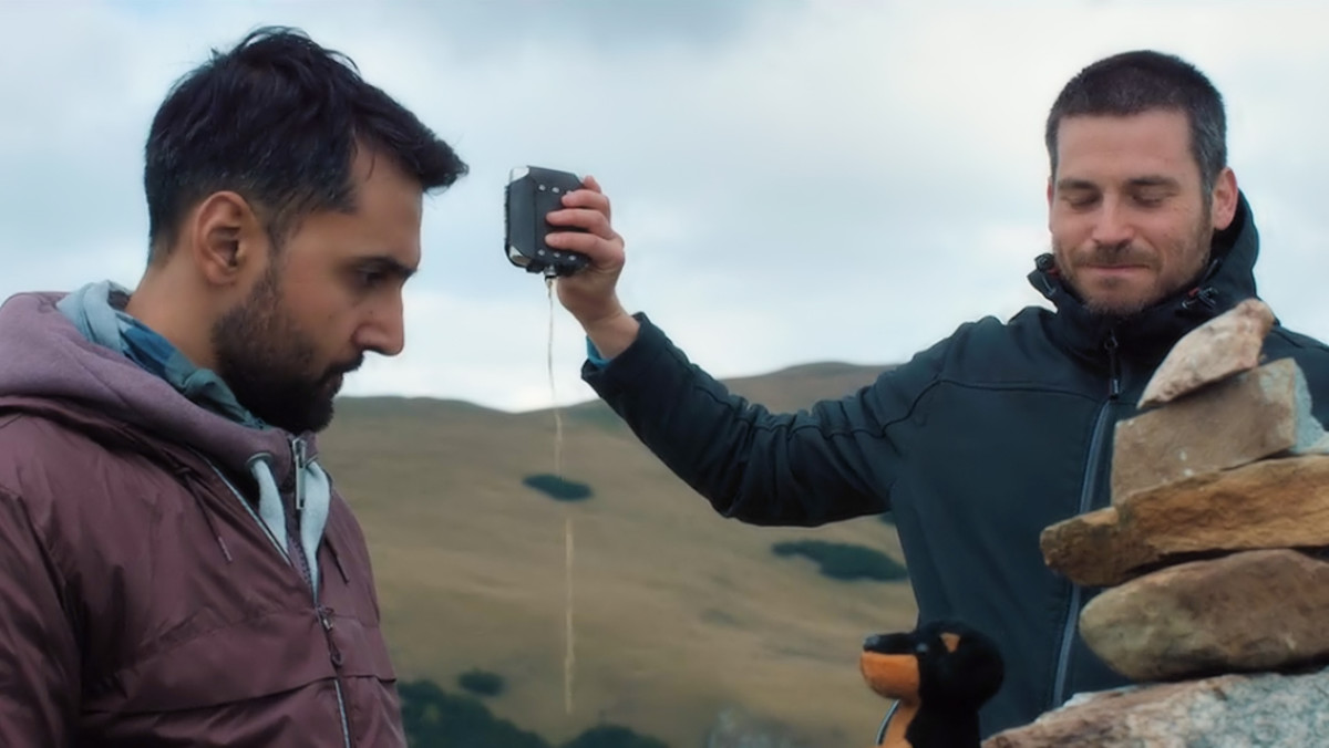 Arsher Ali as Phil and Rob James-Collier as Hutch pour one out in honor of their friend, Robert, in 'The Ritual' (2018), a Netflix Original.