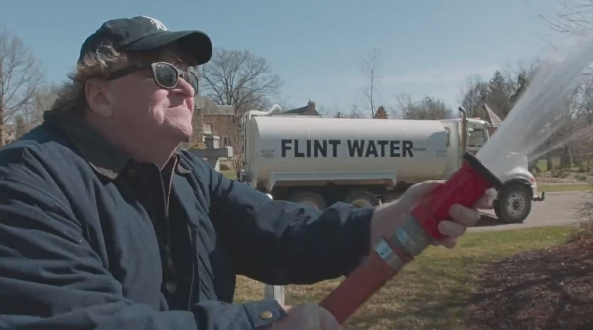 Moore hosing the contaminated water of Flint on the Governor's front lawn.