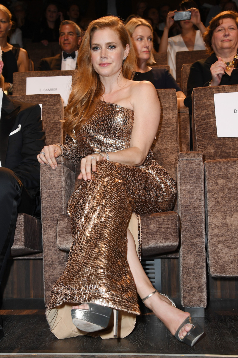 Amy Adams attending an award show in a one shoulder gold dress and sky high platform sandals