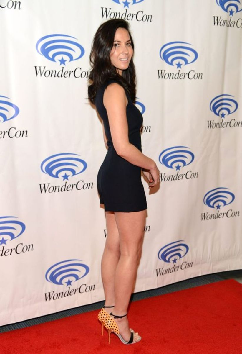 Olivia Munn in a black romper and ankle strap high heels on the red carpet
