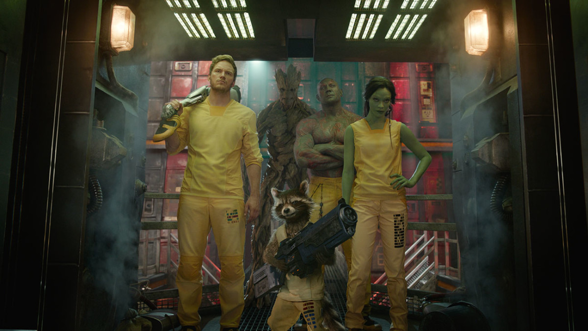 Starlord, Groot, Rocket, Drax and Gamora in full prison uniforms. Weapons aren't prison-issue...