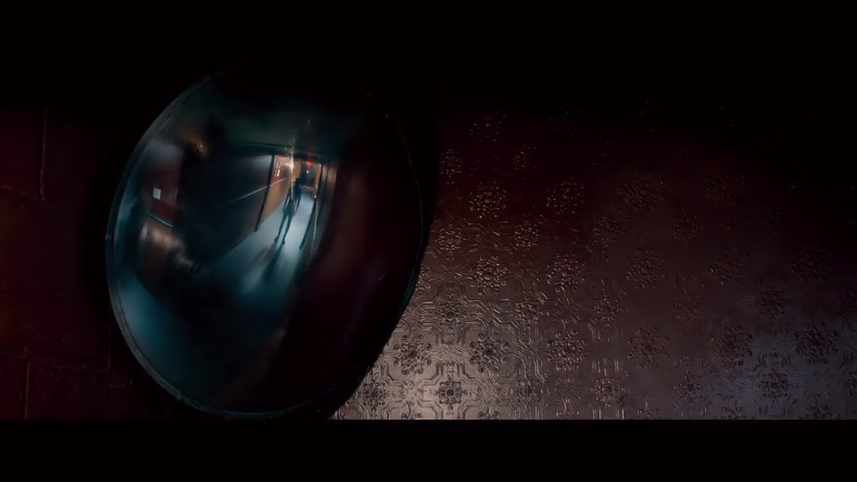 A figure appears in a hallway security mirror inside the Tilden Morgue.  'The Autopsy of Jane Doe' (2016)