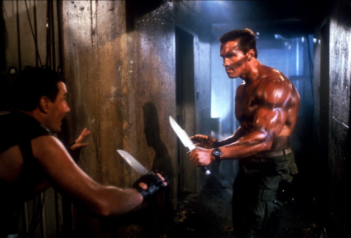 Wells (left) is an oddly camp baddie opposite the mountain of meat that is Arnie (right)...