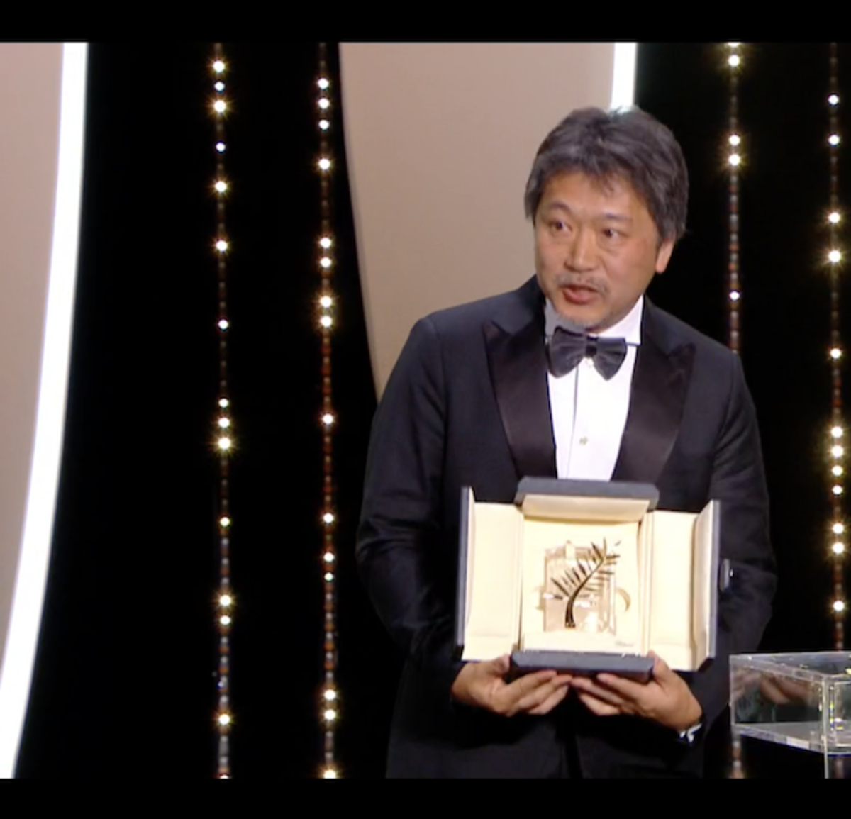 Director Hirokazu Kore-eda, seen here with his Palme D'Or award for the film, creates a heartwarming portrait of an unconventional family struggling to survive as well as stay together.