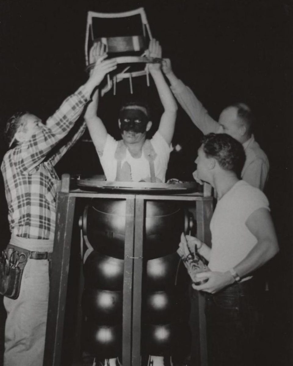 Actor putting on Robby the Robot suit